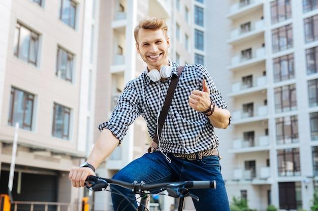È tutto perfetto. felice uomo gioioso che mostra segno giusto mentre si guida una bicicletta