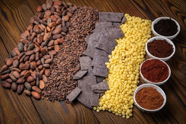 Tutti i tipi di fave di cacao grattugiate pressate e burro di cacao su un tavolo di legno