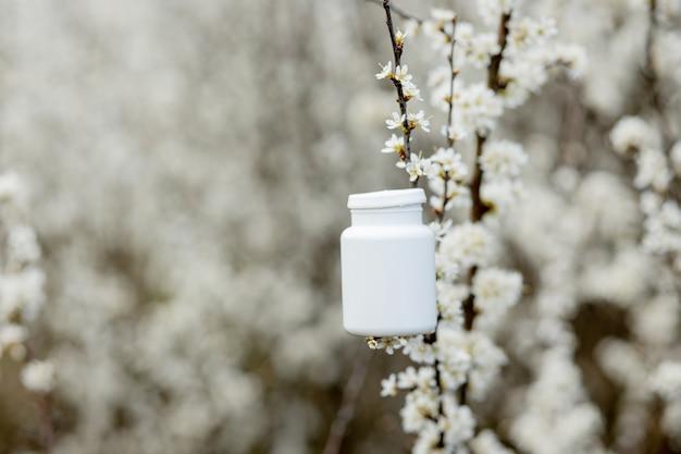 Pillole di allergia sullo sfondo di piante in fiore.
