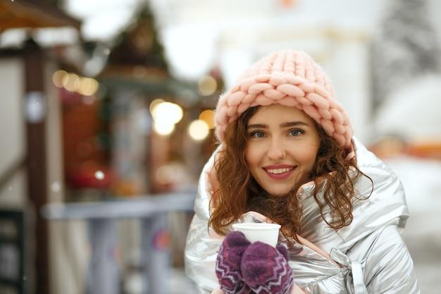 Seducente donna bruna che indossa berretto lavorato a maglia e cappotto caldo che beve caffè caldo alla fiera invernale. spazio per il testo