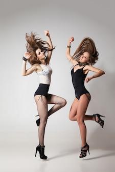 Donne che ballano go-go seducenti in posa su sfondo grigio