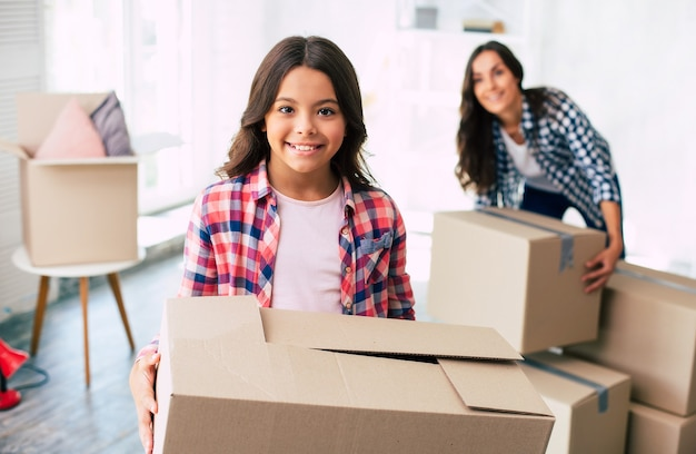 La seducente giovane donna e suo figlio tengono in mano scatole di cartone nella loro nuova casa dopo il trasferimento