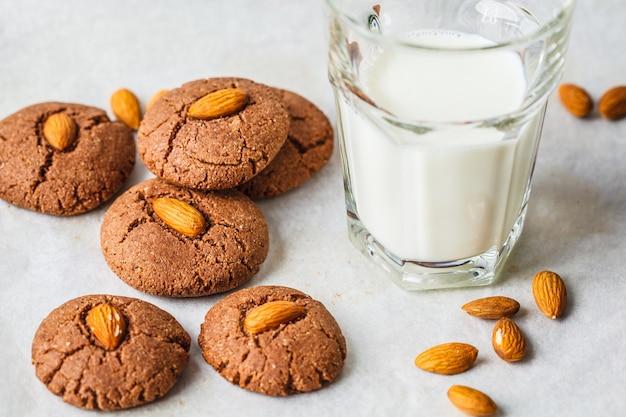 Biscotti al cioccolato alle mandorle con latte su uno sfondo bianco