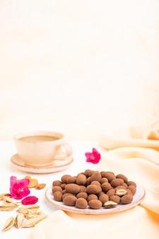 Mandorle in confetti al cioccolato su piatto in ceramica e una tazza di caffè su una superficie di cemento bianco e tessuto di lino arancione