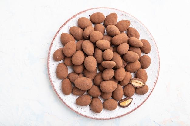 Mandorle in confetti al cioccolato sul piatto in ceramica su sfondo bianco di cemento. vista dall'alto, da vicino, laici piatta.