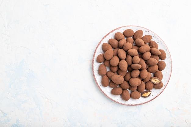 Mandorle in confetti al cioccolato sul piatto in ceramica su una superficie di cemento bianco