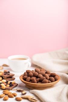 Mandorle in confetti al cioccolato in piatto di legno e una tazza di caffè sulla superficie bianca e rosa e tessuto di lino