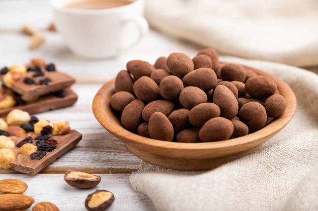 Mandorle in confetti al cioccolato nel piatto di legno e una tazza di caffè su fondo di legno bianco e tessuto di lino. vista laterale, messa a fuoco selettiva.