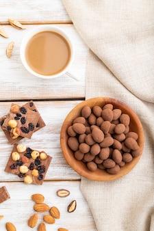 Mandorle in confetti al cioccolato in piatto di legno e una tazza di caffè su superficie di legno bianca e tessuto di lino