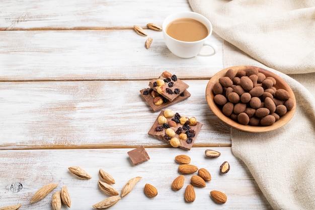 Mandorle in confetti al cioccolato nel piatto di legno e una tazza di caffè