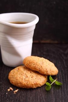 Biscotti di mandorle su uno sfondo nero con una tazza di caffè
