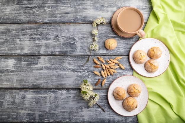 Biscotti alle mandorle e una tazza di caffè su uno sfondo di legno grigio e tessuto di lino verde. vista dall'alto, piatto laico, copia dello spazio.