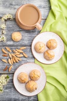 Biscotti alle mandorle e una tazza di caffè su un tavolo in legno grigio e tessuto di lino verde. vista dall'alto, piatto laico, da vicino.