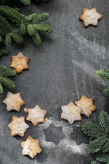 Biscotti alle mandorle con zucchero a velo, con rami di albero di natale su sfondo scuro.