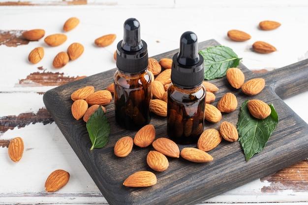 Olio essenziale di mandorle in bollicine di vetro scuro e noci di mandorle fresche.