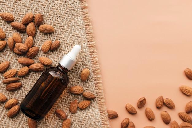 Olio essenziale di mandorle in bottiglia di vetro, mandorle crude in chicchi. concetto cosmetico su sfondo beige con tela di sacco, isolato laici piatta.