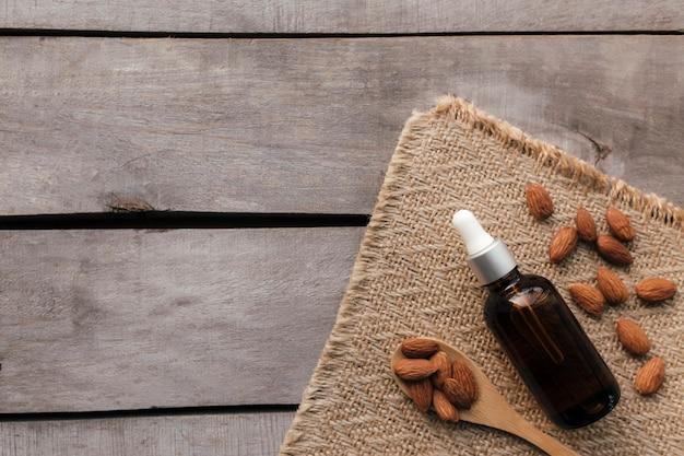 Olio essenziale di mandorle in bottiglia di vetro con cucchiaio. concetto cosmetico su sfondo di legno con tela di sacco, isolato laici piatta.