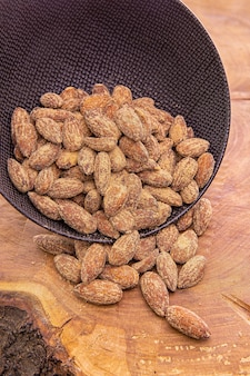 Noccioli di mandorle cosparsi di noci salate versate da una tazza scura su un tavolo di legno