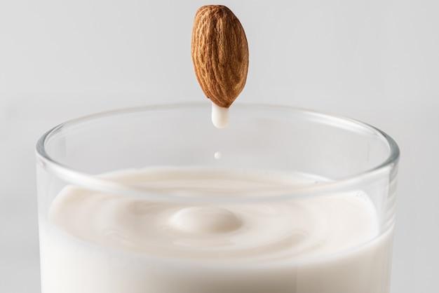 Goccia di latte di mandorle che scorre dalla noce intera nel bicchiere pieno di latte vegetale