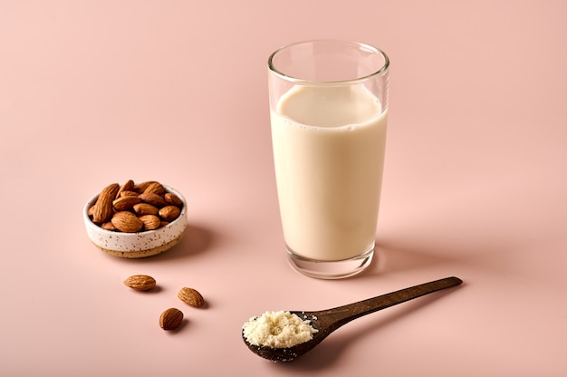 Latte di mandorle in farina di vetro in cucchiaio di legno marrone e gherigli di noci su fondo rosa in polvere selettivo