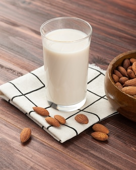 Latte di mandorle nel bicchiere con mandorle in ciotola di legno sul tavolo, spuntino sano, cibo vegetariano.