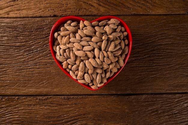 Mandorle dentro un vaso di cuore su fondo di legno