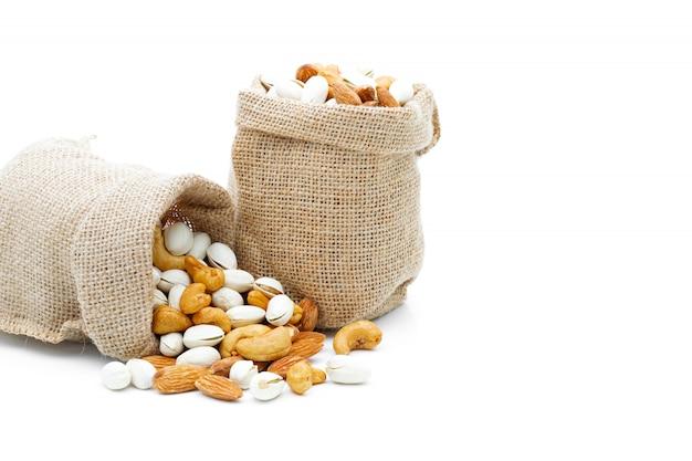Pistacchio e anacardi delle mandorle in un sacco su un bianco isolato