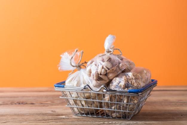 Mandorle, noci, anacardi in sacchetti di plastica in un cestino della spesa