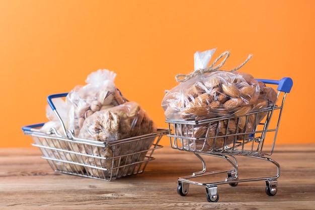 Mandorle, noci, anacardi in sacchetti di plastica in un carrello della spesa e in un cestino