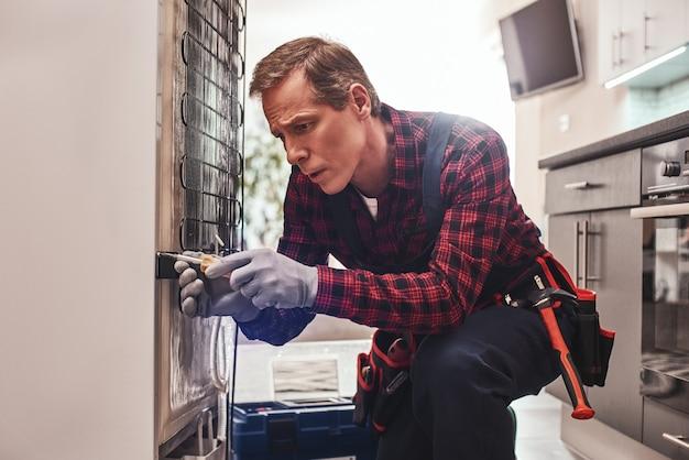 Quasi finito tecnico maschio senior che controlla il frigorifero