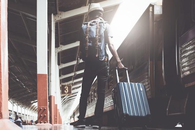 Solo asiatici in viaggio con zaino in spalla e valigia per viaggiare in treno in thailandia