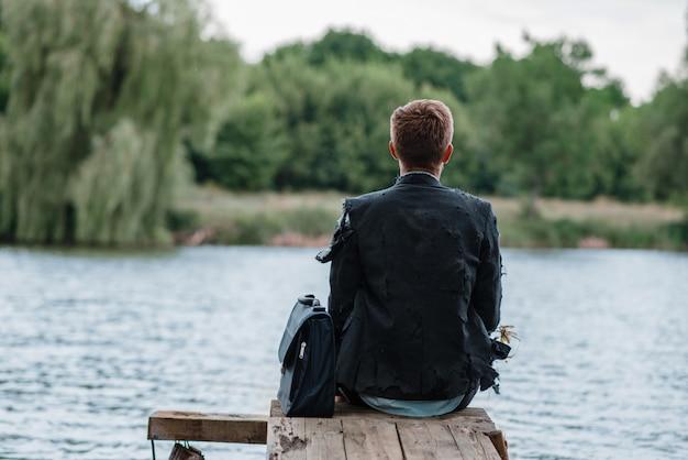 Uomo d'affari da solo seduto sul molo, isola perduta