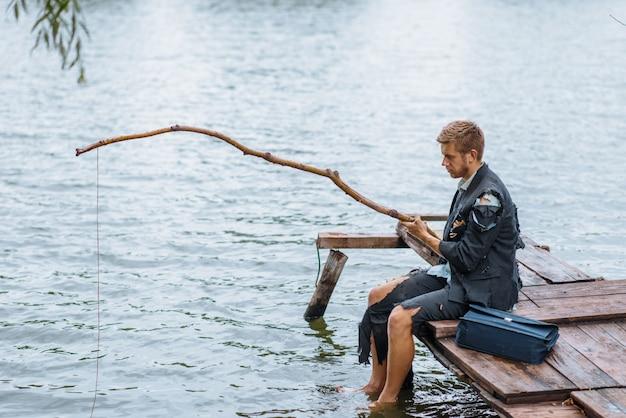 Uomo d'affari da solo in abito strappato pesca sull'isola perduta. rischio aziendale, crollo o concetto di fallimento