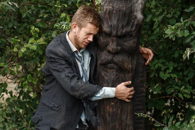 Uomo d'affari da solo in vestito strappato abbraccia la statua di legno su un'isola deserta. rischio aziendale, crollo o concetto di fallimento