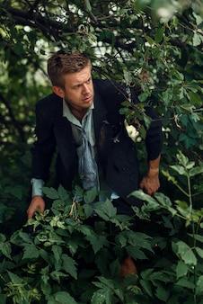 Uomo d'affari da solo in abito strappato che si fa strada attraverso la foresta su un'isola deserta. rischio aziendale, crollo o concetto di fallimento