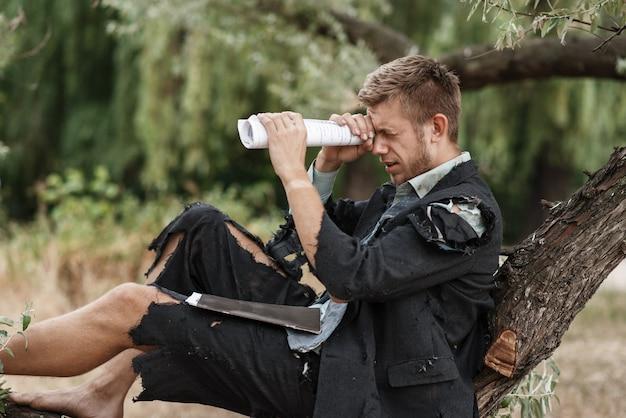 Uomo d'affari da solo in vestito strappato che riposa sull'albero sull'isola perduta.