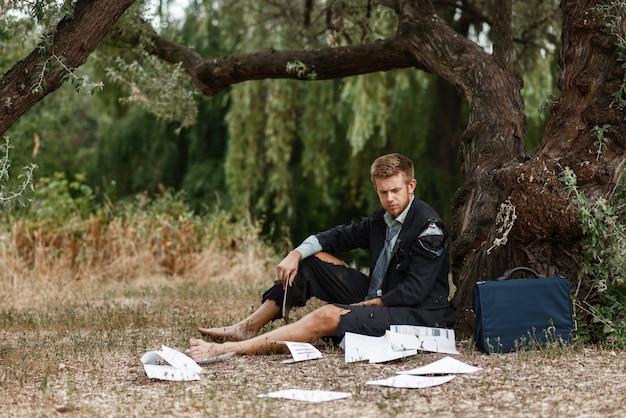 Uomo d'affari da solo in vestito strappato seduto per terra sull'isola perduta.