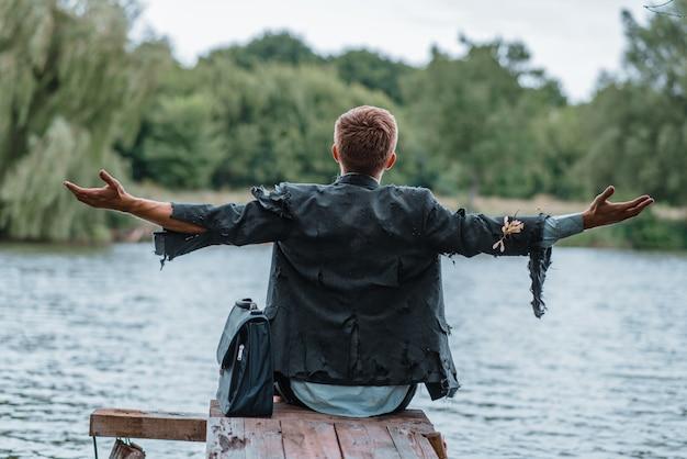 Uomo d'affari da solo in vestito strappato che si siede sul molo sull'isola perduta, vista posteriore.