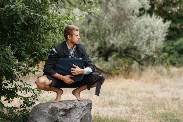 Uomo d'affari da solo in vestito strappato che si siede sulla pietra sull'isola perduta.