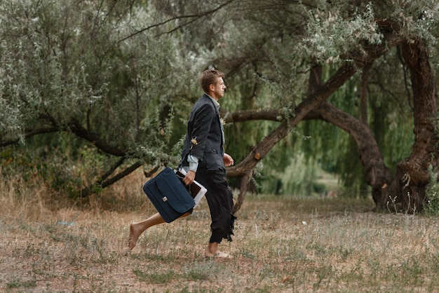 Uomo d'affari da solo in vestito strappato che cammina sull'isola deserta.