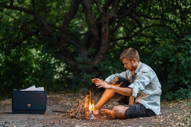 L'uomo d'affari da solo si riscalda accanto al fuoco sull'isola perduta.
