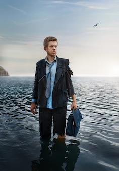 Uomo d'affari da solo con valigetta in piedi nel mare, isola deserta.