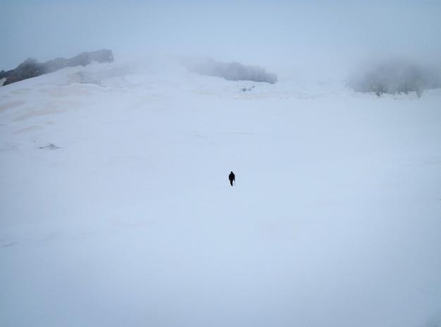 Scalatore da solo che sale alla montagna nevosa nella nebbia