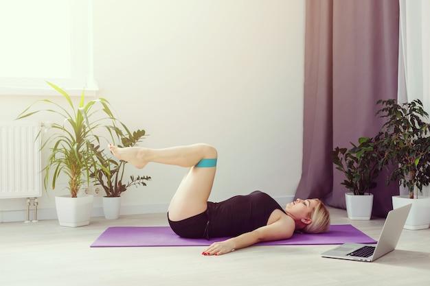 Ragazza sola che fa esercizi di yoga online sul laptop sul pavimento nella stanza luminosa, resta a casa al sicuro nel mondo.