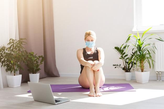 Ragazza sola in maschera medica che fa esercizi di yoga sul pavimento nella stanza luminosa durante la quarantena del covid 19 cotonavirus resta a casa mondo sicuro.
