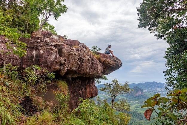 Uomo solo seduto sul bordo della scogliera e guardando il paesaggio vista foresta pluviale dragon crest