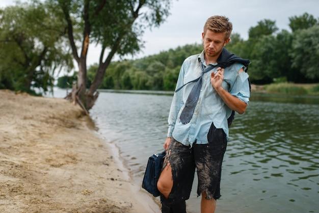 Impiegato da solo in vestito strappato che cammina sulla spiaggia sull'isola deserta.