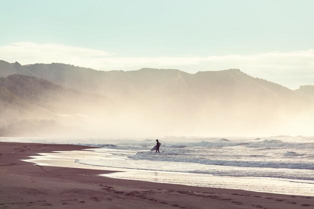 Surfista da solo sulla spiaggia dell'oceano in nuova zelanda