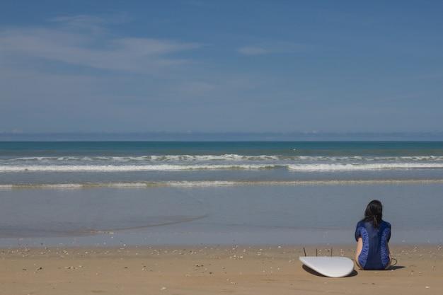 Donna sola con una tavola da surf che si siede sulla spiaggia