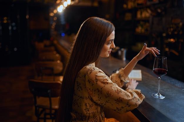 Giovane donna sola con un bicchiere di vino rosso seduto al bancone del bar. una donna in un pub, emozioni umane, attività ricreative, vita notturna
